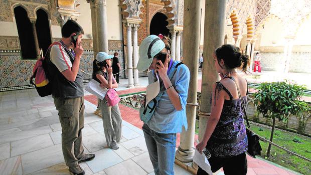 Varios turistas pasean por el Alcázar siguiendo las indicaciones de las audioguías