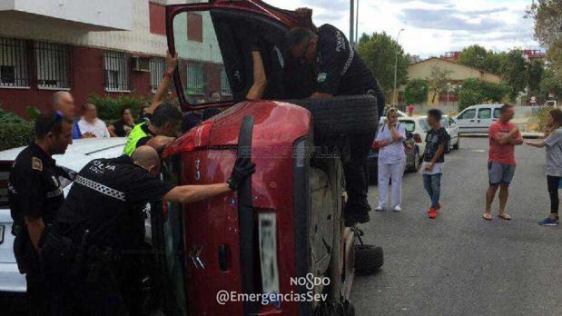 La Policía tratando de asistir al conductor del vehículo volcado