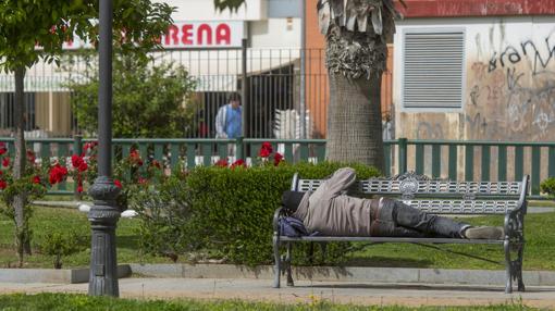 Un indigente reposa en un banco del parque de los Perdigones