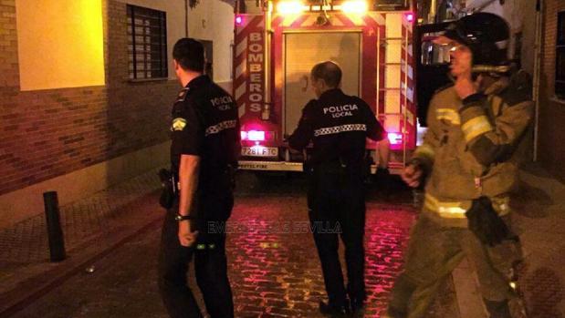 Agentes de la policía local y bomberos, en el incendio de un bar en Triana