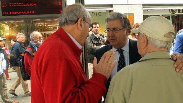 El portavoz del PP en el Ayuntamiento de Sevilla, Juan Ignacio Zoido, con vecinos en una parada de Tussam