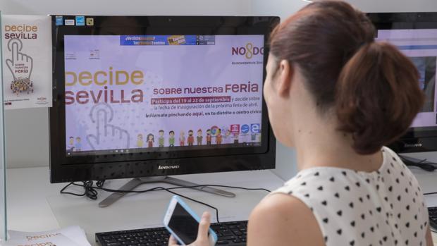 Una empleada municipal ante la web abierta «Decide Sevilla» para votar de forma telemática sobre la Feria de Abril