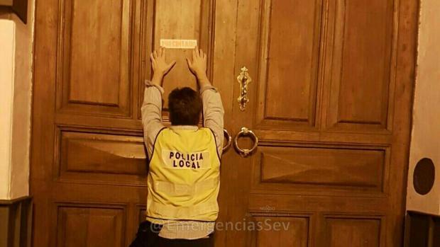Un agente coloca el cartel que anuncia el precinto en la puerta de la discoteca