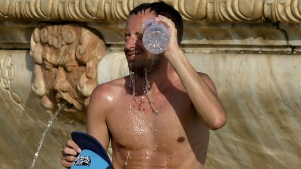 Un joven se refresca en la plaza de España de Sevilla