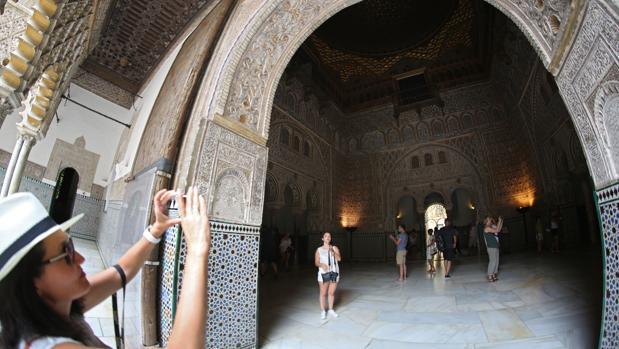 Una turista fotografía un detalle de una sala del Real Alcázar