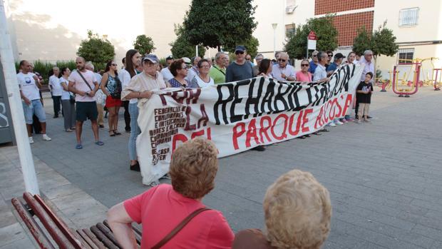 Varios vecinos se situan tras la pancarta con la que se manifestaron en Alcosa