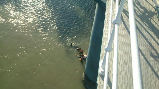 Rescate del motorista y el policía local en el río