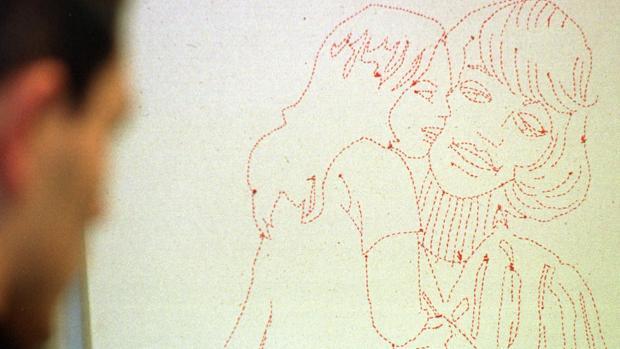 Un hombre mira un grabado de una mujer y una niña en una exposición en Sevilla