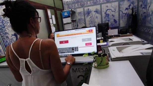 Una mujer realiza el proceso de votación en un centro cívico