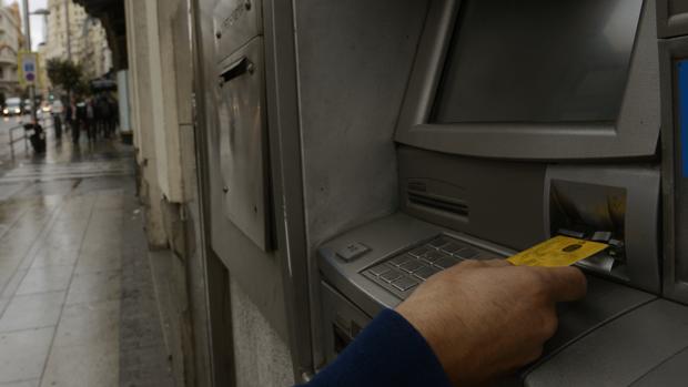 Un hombre saca dinero de un cajero en la vía pública