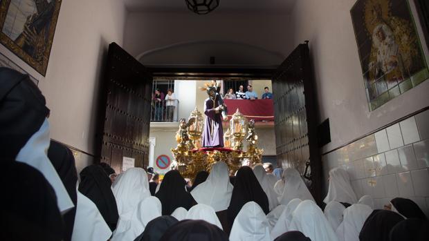 Las hermanas de la Cruz rezan ante el Señor detenido en las puertas del convento en la calle Santa Ángela