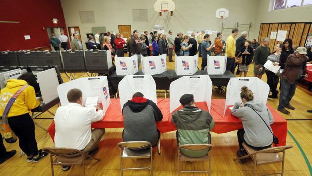 Votantes estadounidenses rellenan sus papeletas en un colegio electoral de Ohio