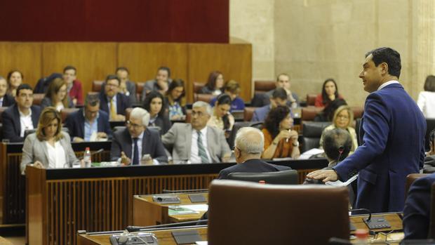 El portavoz del PP andaluz, Juanma Moreno, en primer plano y al fondo el Gobienro andaluz, en el Parlamento