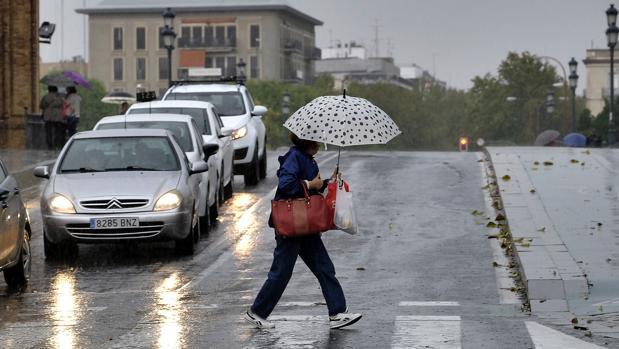 Una mujer se protege de la lluvia con un paraguas en el puente de Triana