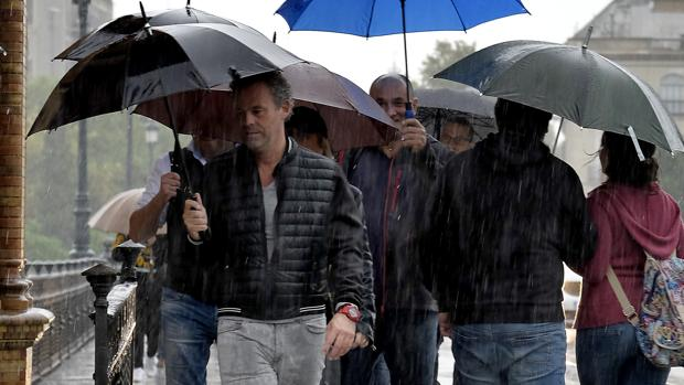 Sevillanos se resguardan de la lluvia bajo sus paraguas