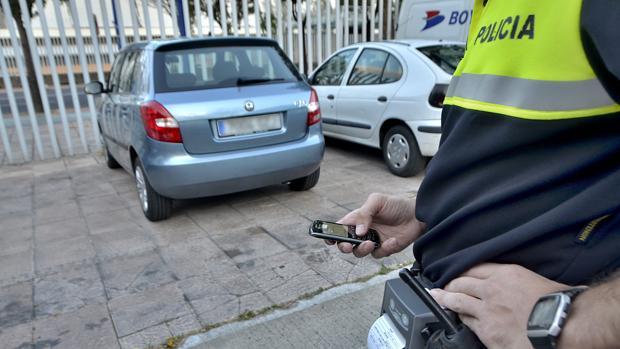 Un policía municipal pone una multa a un vehículo mal estacionado con su dispositivo móvil
