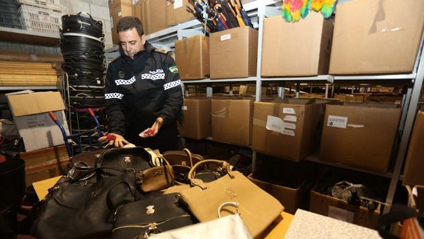 Un agente de la Policía Local de Sevilla con bolsos falsos