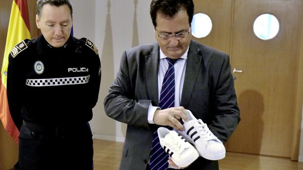 El delegado de Seguridad, Juan Carlos Cabrera, mostrando un par de zapatillas