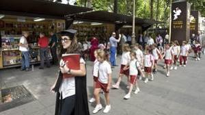 Alumnos guiados por una educadora en una visita a una edición anterior de la Feria del Libro de Sevilla