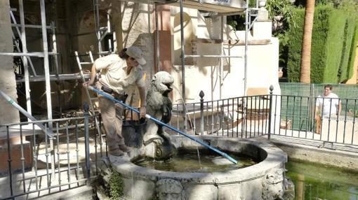 Una trabajadora limpia el surtidor del León