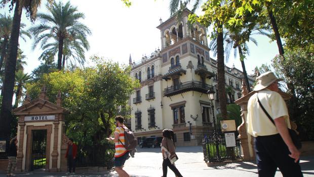 Varios turistas pasean ante la entrada del hotel Alfonso XIII