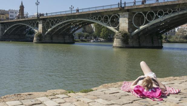 Una mujer toma el sol a la altura del puente de Triana
