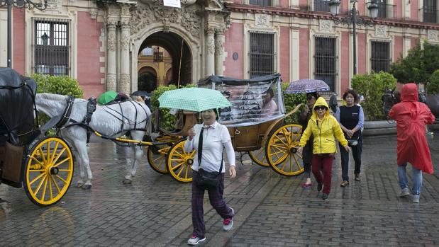Turistas por el centro de Sevilla bajo la lluvia