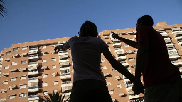 Una pareja señalan una vivienda en un residencial