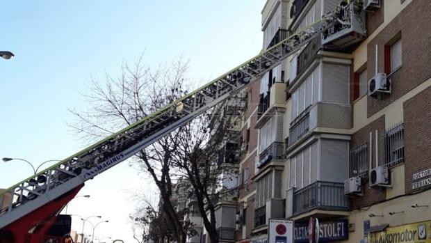 Los bomberos entranado con la grúa articulada en la casa