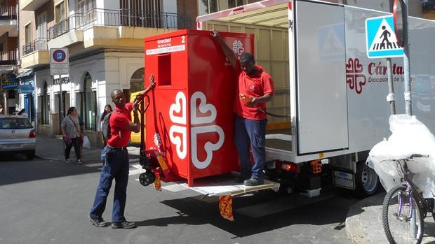 Dos empleados de Cáritas recogen un contenedor de ropa