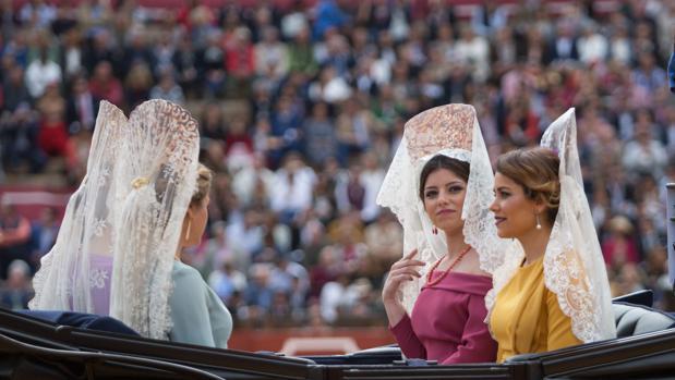 Unas jóvenes atavidas con la mantilla blanca española pasean en su carruaje en la Maestranza