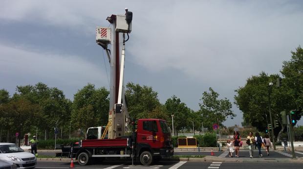 Operarios cambian los proyectores de una de las columnas de luz de la avenida Torneo