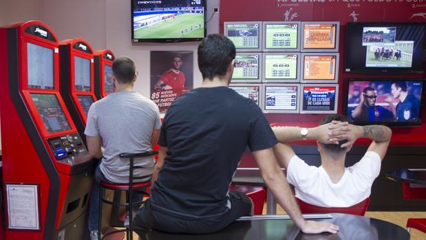 Varios jóvenes, ante las pantallas de apuestas deportivas de un salón de juegos
