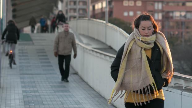 Una joven camina por Sevilla bien abrigada