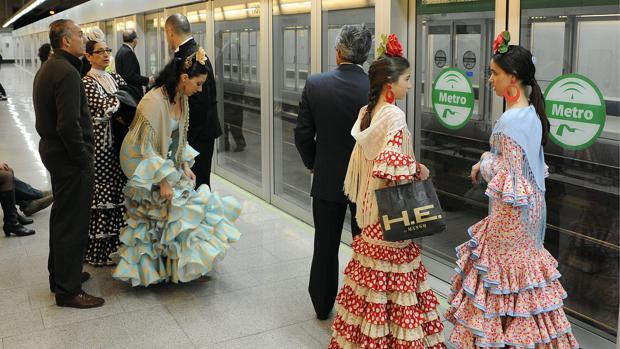 Personas esperando en la parada de metro para ir a la Feria de Abril