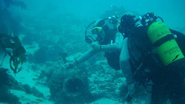 Una pareja de buzos rastrean la zona de un yacimiento subacuático