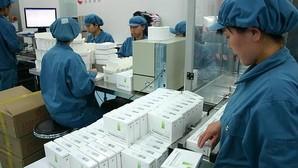 Un grupo de trabajdores chinos revisan la fabricación de vacunas