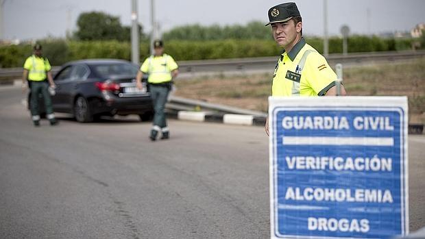 Varios agentes de la Guardia Civil de Tráfico preparan un control de alcoholemia y drogas este mediodía en la localidad de Puçol (Valencia)