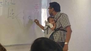 Un profesor universitario sostiene al bebé de una alumna para que pueda tomar apuntes durante la clase