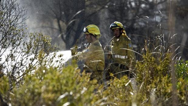 Efectivos del cuerpo de Bomberos durante las labores de extinción del incendio forestal en la zona de Coves Noves, en Arenal d'en Castell, en el norte de Menorca, que ha obligado a desalojar a cerca de 600 personas que viven en estos núcleos residenciales del municipio de Es Mercadal