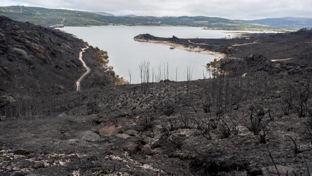 En la imagen, vista del embalse de Salas y de superficie calcinada en el incendio forestal de Entrimo, en Orense, que es, en este momento, el de mayor envergadura de los registrados en Galicia, con 2.800 hectáreas arrasadas, y se mantiene como medida preventiva la situación dos, por su proximidad a las viviendas