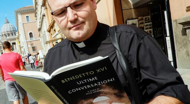 Un párroco lee las memorias del Papa emérito Benedicto XVI, hoy en la avenida próxima al Vaticano
