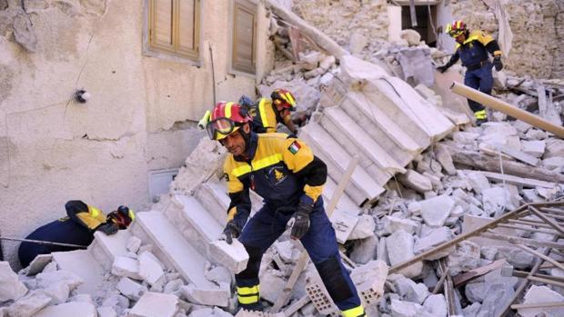 Varios bomberos trabajan entre los escombros producidos por el terremoto en Pescara del Tronto