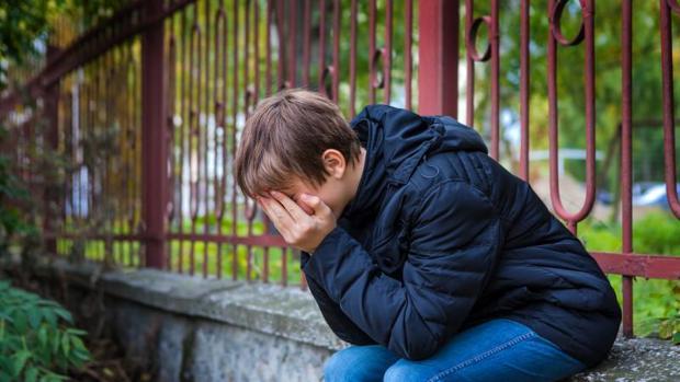 Un niño llora tapándose la cara en la calle