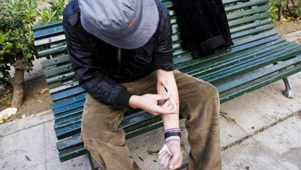 Un adicto se inyecta heroína en un parque