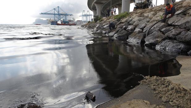 Un camión cisterna absorbe el vertido que se encuentra en la playa de la Concha en Algeciras, hasta donde ha llegado el derrame de crudo, de 500 litros mezclado con agua, causado por un fallo mecánico en una monoboya (almacén flotante de crudo) de Cepsa en la Bahía de Algeciras