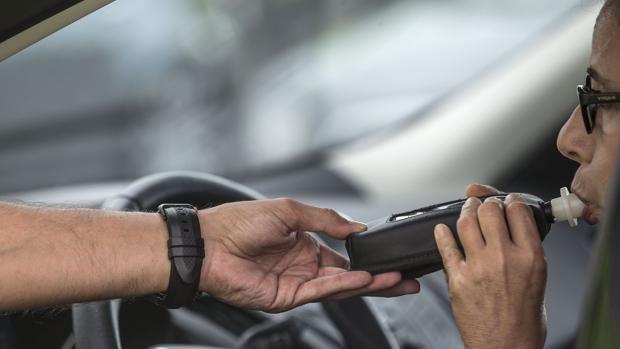 Una conductora realiza la prueba de alcoholemia, en la vía de servicio de la V-31 cerca de Valencia, en un control de la Guardia Civil de Tráfico con motivo de la campaña puesta en marcha por la DGT sobre control de la tasa de alcohol y presencia de drogas en conductores