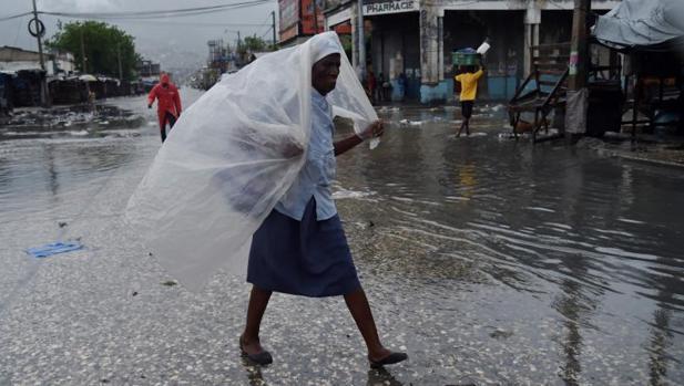 Una mujer se protege de la lluvia tras el paso del huracán Matthew por Haití