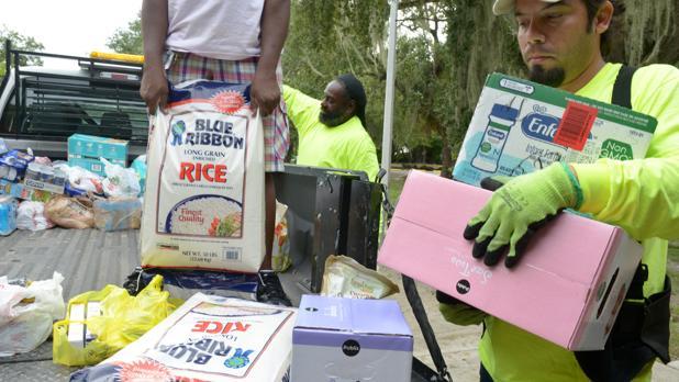 El voluntario José Martinez (d), residente del área de la Pequeña Haití en la ciudad de Miami (Florida), colabora con otros compañeros en el acopio de alimentos, ropa y agua para enviar a Haití, como parte de la ayuda solidaria a ese país
