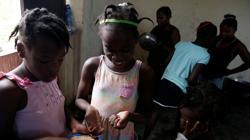 Dos niñas comparten plato en un orfanato de Haití